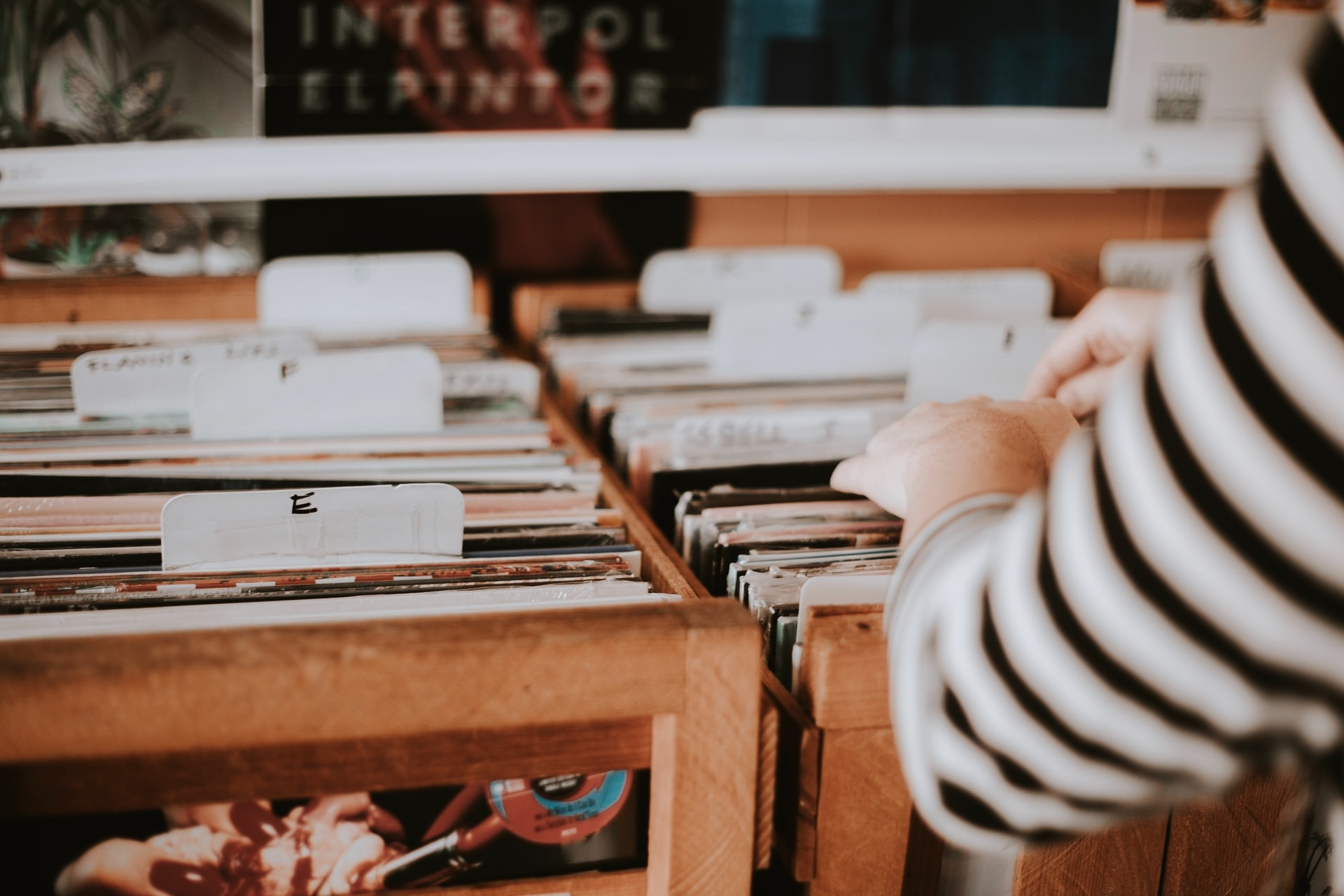 Woman browsing vinyl records in crate of record store