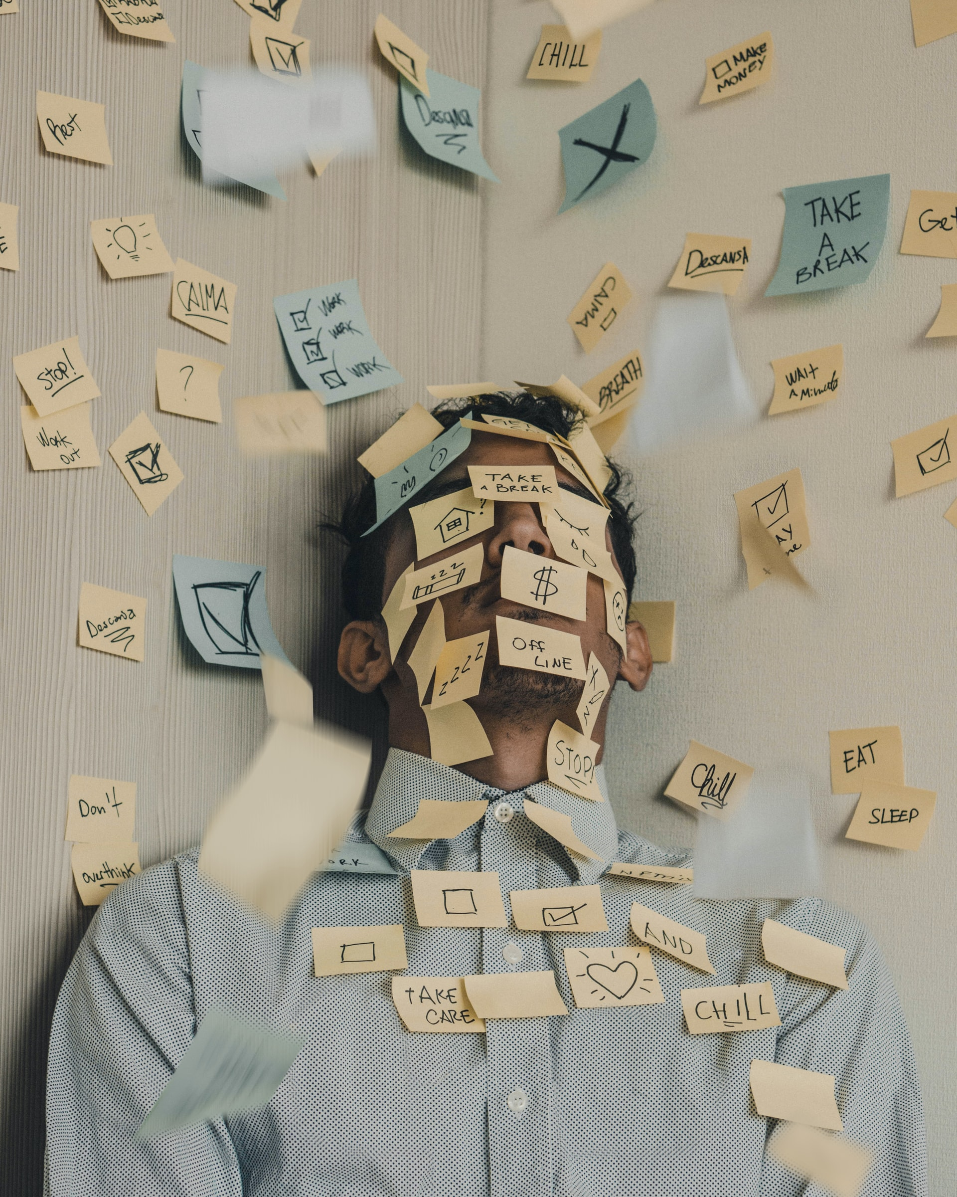 Man in a corner covered by post-it notes all over his face