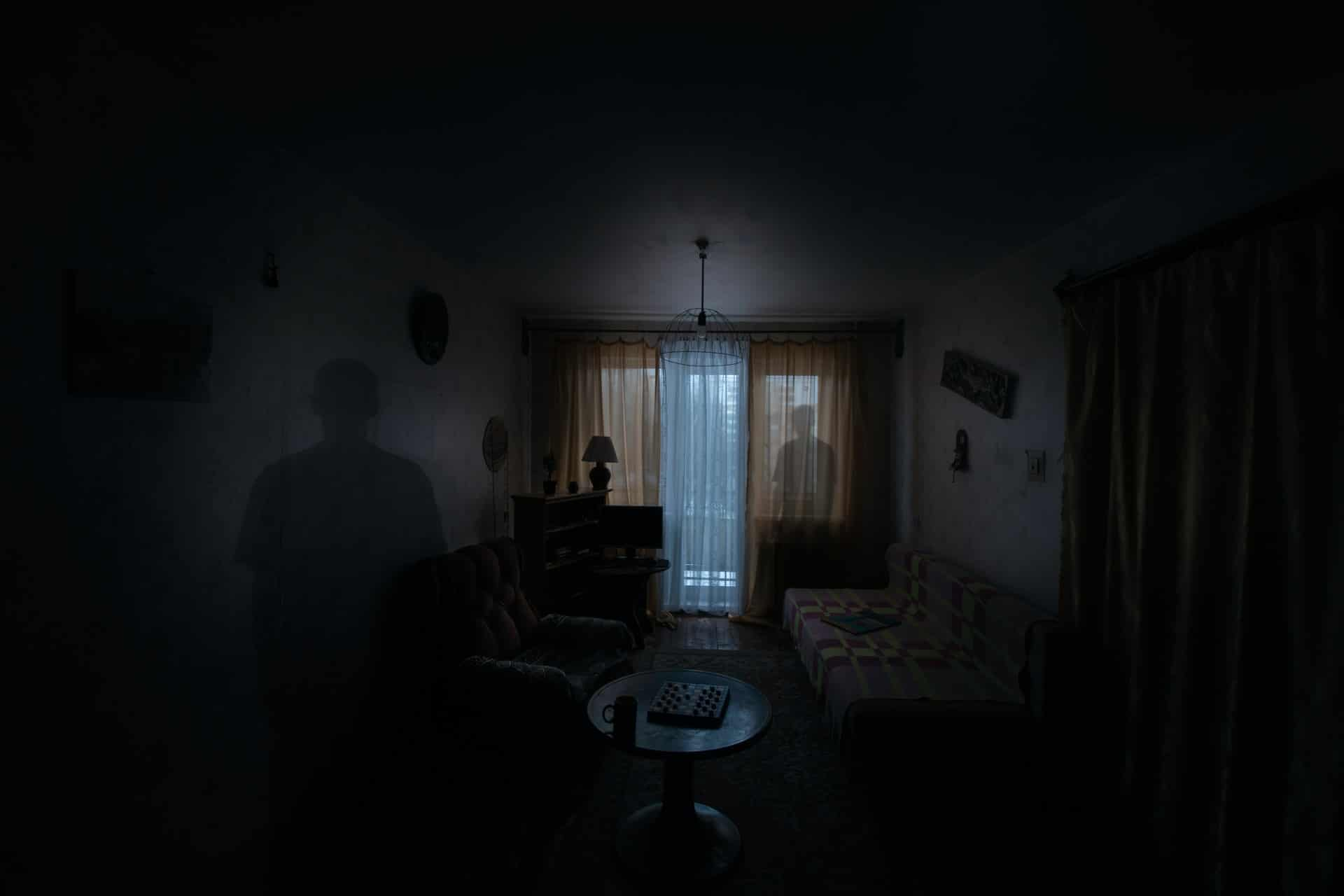 Man standing in dark room with his faded after image